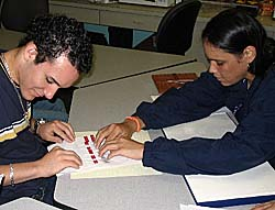 Wanda Diaz helps a student read a book that is written in Braille