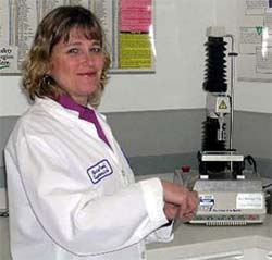 Michele Perchonok stands in the food lab with a piece of equipment on the counter beside her