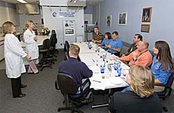 Michele Perchonok stands and talks to astronauts who are seated around a table with cups, plates and utensils
