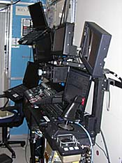 A workstation featuring several computers and a joystick