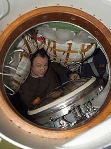 ISS014-E-18789 -- Astronaut Michael Lopez-Alegria is photographed through a hatch in the Soyuz 13 (TMA-9) spacecraft