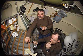 ISS014-E-18790 - Expedition 14 crew members share a meal