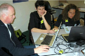 Teachers sitting at a table working with computers in a classroom