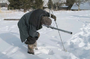 Phil Farnes using a scientific measuring tool in the snow