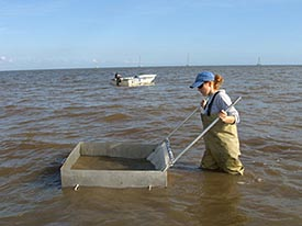 Lissa Lyncker stands in knee-deep water as her boat floats in the background