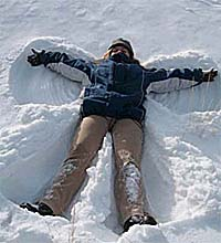 Woman lying in the snow making a snow angel