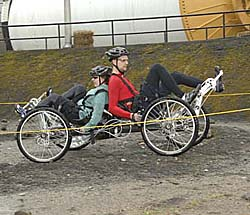 Two students on moonbuggy -- one facing forward, one facing backward