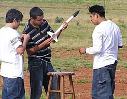 Three students assembling rocket