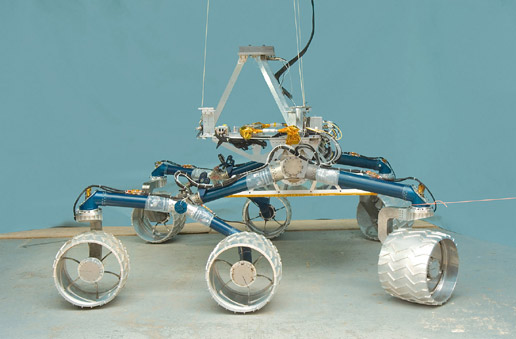 In this image, a large, six-wheeled rover sits on a concrete floor in a laboratory against a light-blue background.