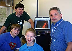Students and teacher in front of a computer displaying a starry image