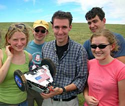 A team of students hold up a small rover