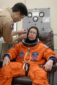 Astronaut Pat Forrester suits up in training for the STS-117 mission.