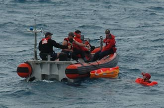 A Coast Guard crew drops off a trainee acting as an astronaut for a rescue exercise.