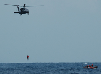 An Air Force HH-60 rescue helicopter pulls a pretend astronaut from the Atlantic Ocean during rescue exercises.