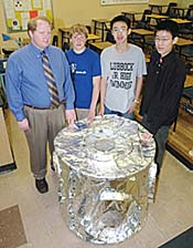 Teacher and students pose with aluminum-foil-covered model
