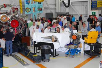 An engineer shows space shuttle program officials the inner workings of the Space Shuttle Main Engines.