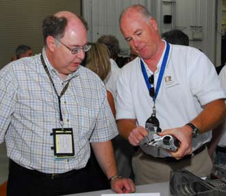 A Rocketdyne official shows Shuttle Program Manager Wayne Hale a piece of the main engine.