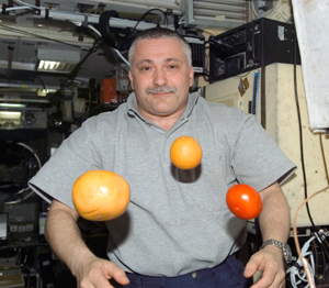 Fyodor Yurchikhin is pictured near fresh fruit floating freely