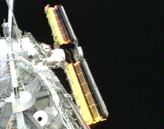 The space station's new solar array wings wait to be fully unfurled