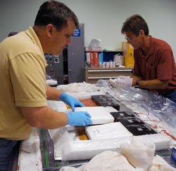 A pair of United Space Alliance workers assemble panels for testing the thermal blankets.