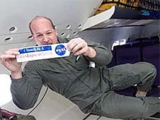 Teacher in green flight suit holding a NASA Explorer School bumper sticker