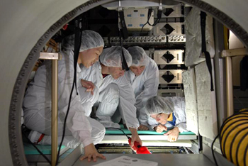 Astronauts in cleanroom suits inspect the SPACEHAB module