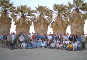 Group posing in front of a row of palm trees
