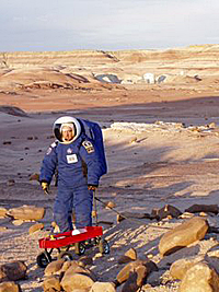 A student in a blue space suit pulls a wagon in the desert