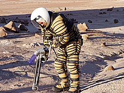 A student uses a tool while wearing a beige and black space suit