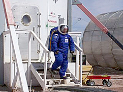 A student wearing the blue NDX-1 space suit walks down stairs in front of the cylindrical habitat module