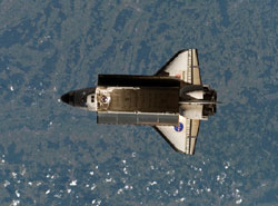 ISS015-E-12838 : Space Shuttle Atlantis backdropped over a colorful Earth