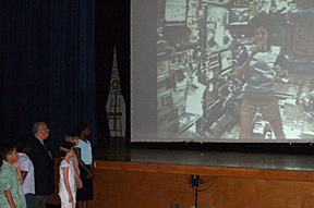 Several students stand in front of a large screen on which Williams is visible