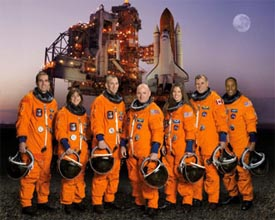 STS-118 crew standing in front of a space shuttle