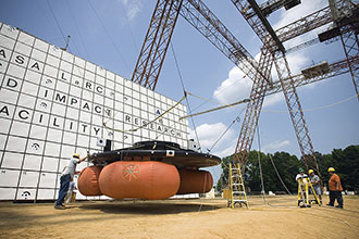 Engineers prepare to lift the Orion test article for a pendulum-swing drop test at the NASA gantry