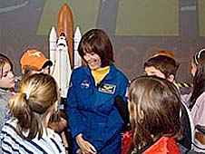 A group of students surround Morgan, who is standing by a model of the space shuttle