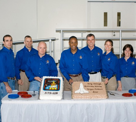 The STS-118 crew poses behind a table with two cakes