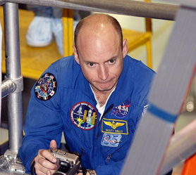 Commander Scott Kelly holds a camera as he looks at a piece of equipment