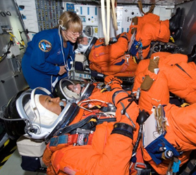 Three astronauts in training versions of orange shuttle launch and entry suits sit in a shuttle simulator with astronaut Hire standing behind them