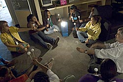 Participants sitting in a circle in a dark room with a bright light in the center