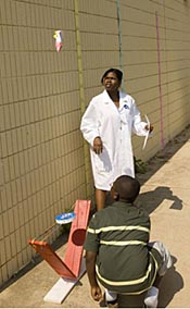 A participant wearing a white lab coat watches a student, kneeling on the ground, launch a rocket