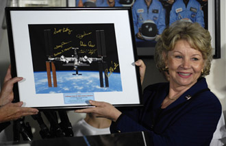 Dr. June Scobee Rogers holds up a signed photo of the International Space Station