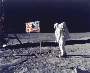 Famous NASA image of the astronaut planting the American flag on lunar soil.