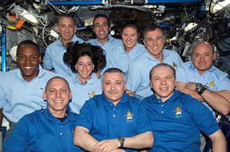 The STS-118 and Expedition 15 crew members gather for a photo.
