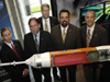 NASA and Boeing management pose for a photo in front of a model of an Ares I rocket.