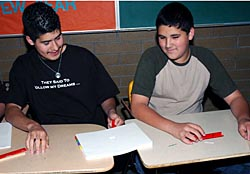 Two students sit at desks trying to move a paperclip on top of a stack of white paper with a red bar magnet underneath the stack