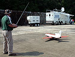 A man with a remote-control device steers a subscale transport airplane on the ground