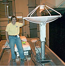 Muller standing next to a white dish antenna