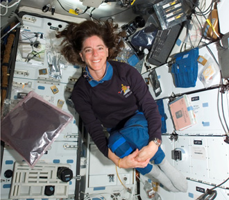 STS-118 mission specialist Barbara Morgan floats with millions of basil seeds she carried to space as part of the Engineering Design Challenge.