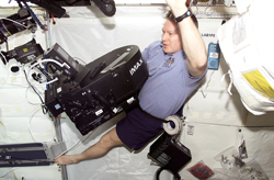 Astronaut Bill Shepherd uses an IMAX camera on the ISS in 2001.