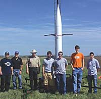 Students and mentors standing in front of rocket